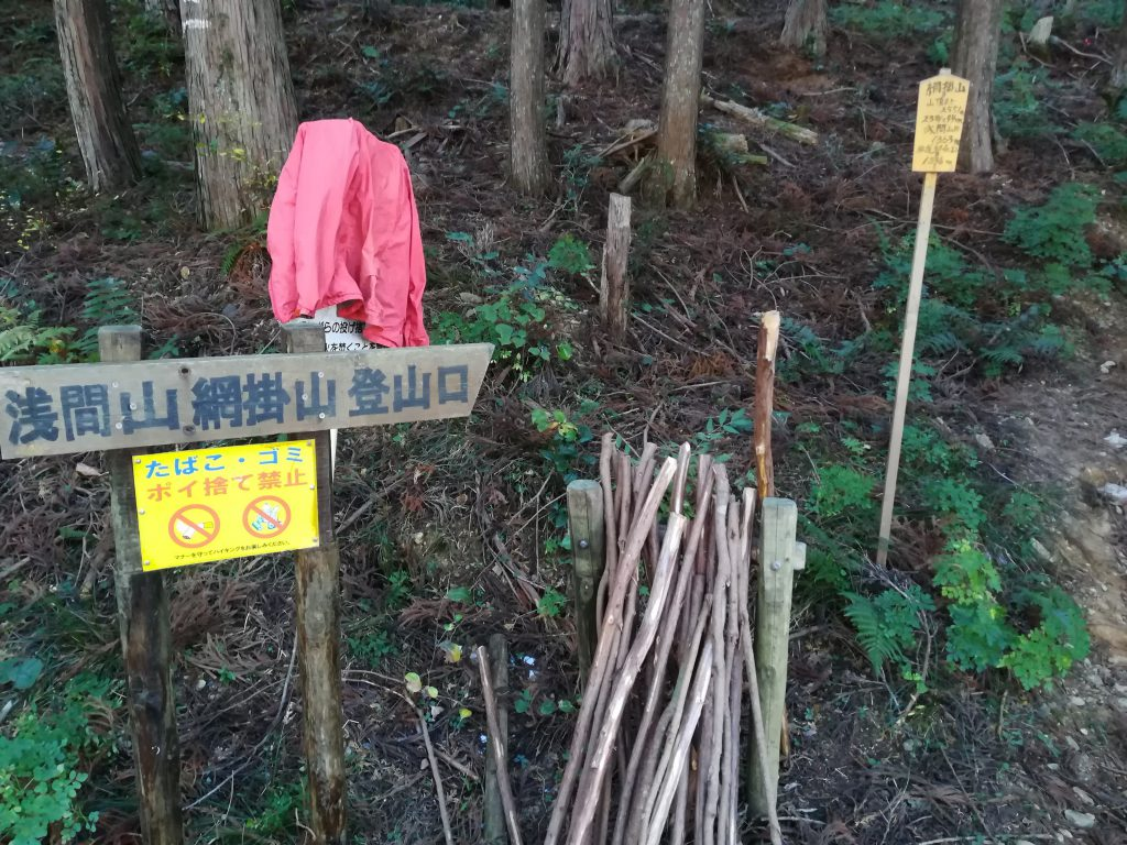 網掛山入り口の案内看板。近くには木製のステッキがあります