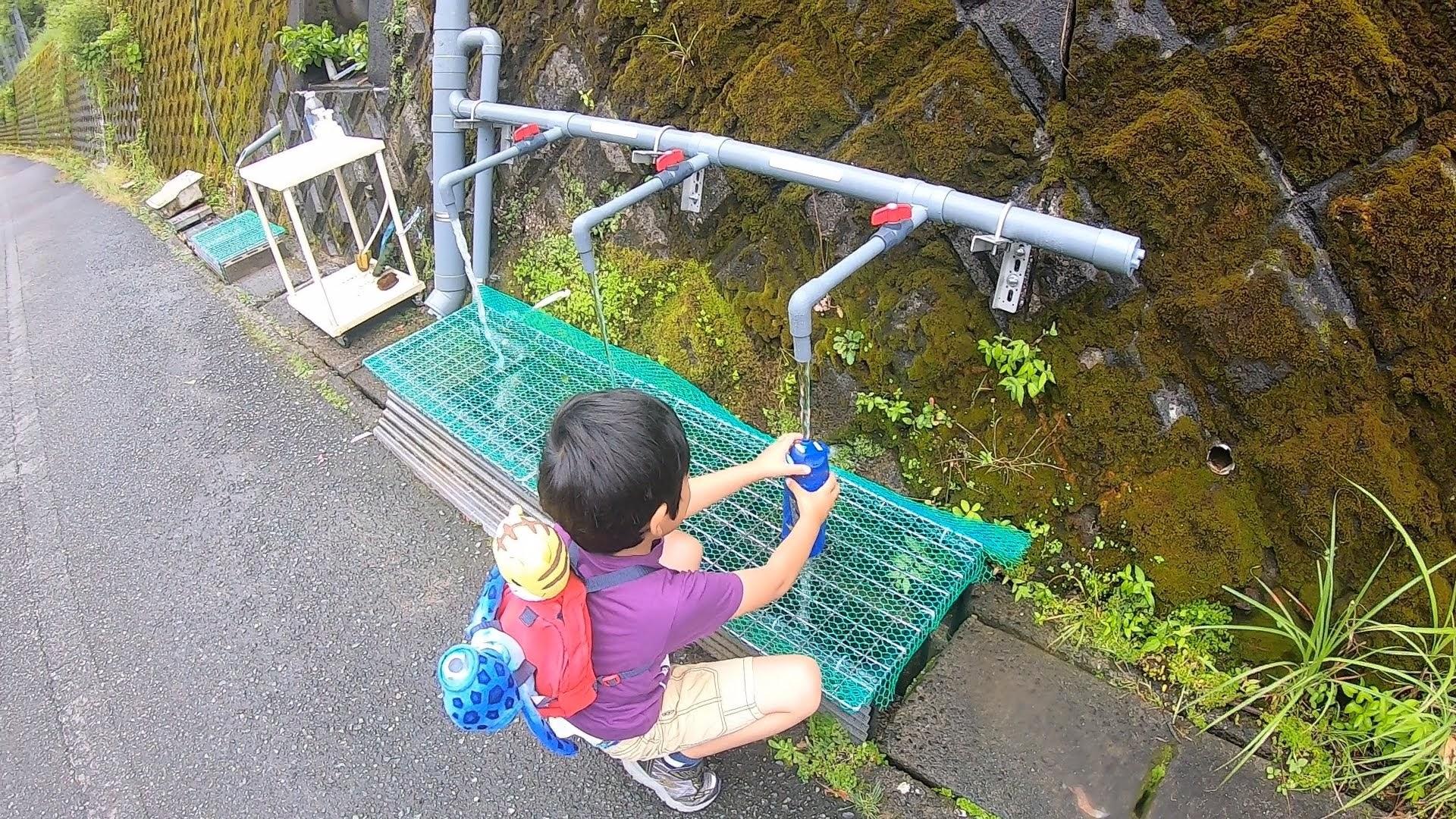 湧き水を汲む子ども